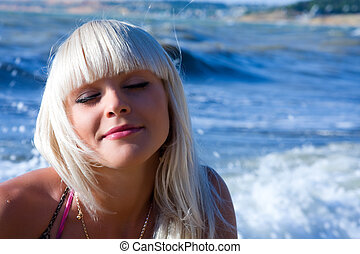 The beautiful blonde the girl against the sea