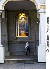 A person walks past a window of the Medhane Alem Cathedral...