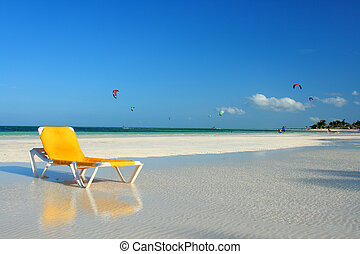 lounge chair on beach by the ocean