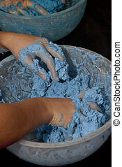 Hands mixing blue coloured paper mache in a mixing bowl