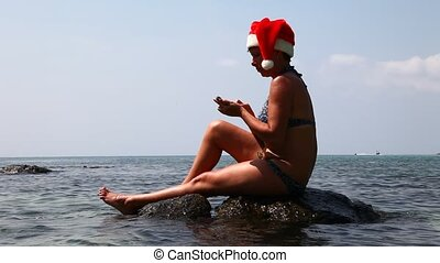 Woman on the beach in santa hat cal