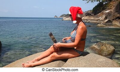 Woman on the beach in santa hat wit