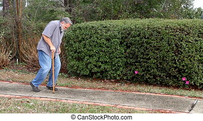 Man With Cane - Old man walks down a sidewalk using a...