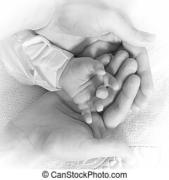 Mothers care - Newborn baby hand being hold with care by...