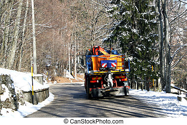 truck with Snowplow and spread salt on the ice in winter -...