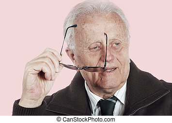 Real people - Senior businessman smiling and holding glasses...