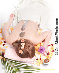Day spa - Young woman getting a hot stone massage in the day...