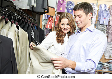 Young peoples shopping at clothes store - Young man and...