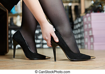 Young woman trying on shoes - Young woman trying on new...
