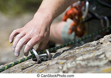Hand of climbing man with carbine and rope - Rock climbing...