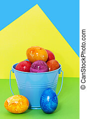 Easter eggs in a bucket on a colored background