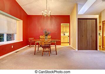 Large dining room with red wall and small wood table. -...
