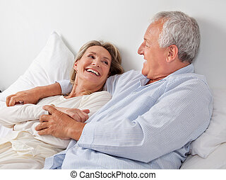 Couple Relaxing in Bed - Cheerful couple relaxing on bed at...