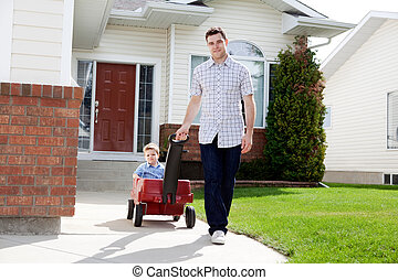 Father Pulling Son Sitting Inside Wagon - Father pulling son...