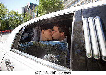 Newlywed Couple Kissing In Limousine