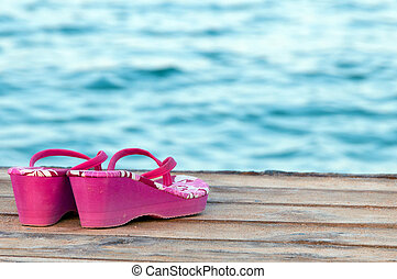 Left - Abandoned sandals at a wooden deck at the beach