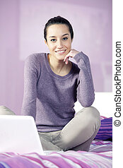 Portrait of a young female relaxing in bed while using laptop