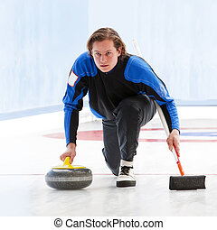 Curling - Skip, delivering a stone, supporting himself by...