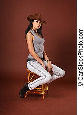 Beautiful girl in jeans clothes and a cowboy hat