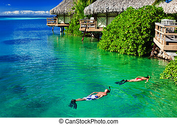 Young couple snorkeling in clean water over reef - Young...