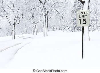 Snow Covered Road - A speed limit sign on a snow covered...