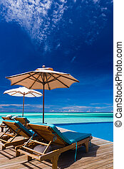 Deck chairs and infinity pool over tropical lagoon - Deck...