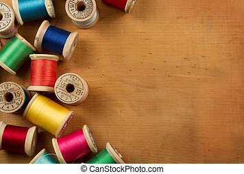 Antique spools of thread on a wooden background - Antique...