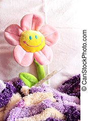 toy flower - Toy is in the flower bed on a pillow covered...