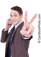 business man making victory sign on phone