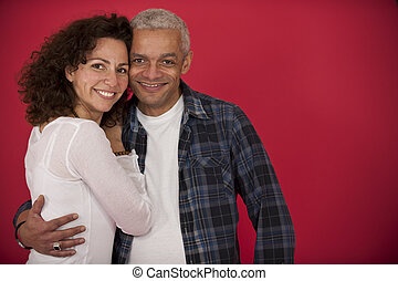 portrait of a mid adult couple hugging on red background