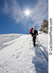 ice climber - A male climber , dressed in black, climbs up a...