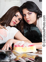 Two girlfriends caress each other in a soapsuds on a bumper of the car