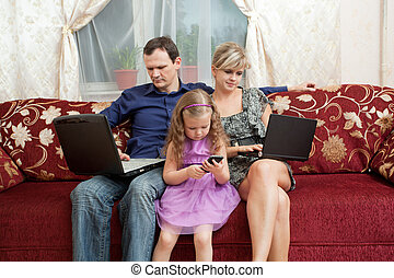 Family of three people sitting on the couch, each with their...