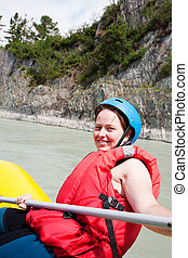 Girl - sportsman on a raft floats on the mountain river