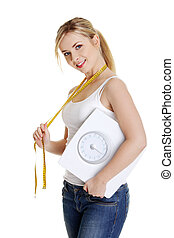 Woman with bathroom scale and measuring tape