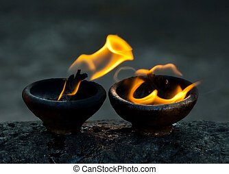 fire amulet - sacred fire, coconut oil lamps in a buddhist...