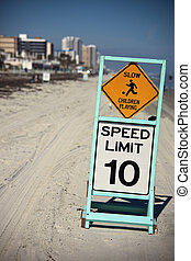 Slow - Children playing. Speed limit - 10. Seen on the beach...