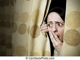 intruder - woman shocked at what she sees behind curtains or...