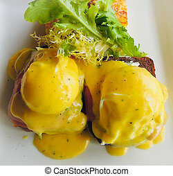 Beautiful eggs benedict with ham and hollandaise sauce is...