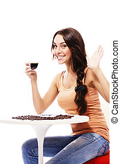 happy young woman sitting at a table holding cup of espresso coffee on white background