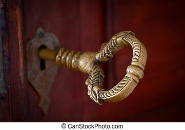 Antique beautiful bronze key in a door. Selective focus on...