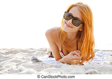 Red-head girl at the beach in sunrise
