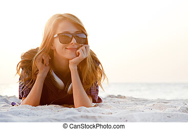 Red-head girl with headphones at the beach in sunrise