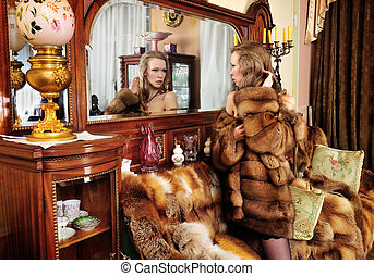 Beautiful naked woman in fur coat  at the mirror. Luxurious classical interior.