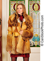 Portrait of the beautiful woman in fur coat. The luxurious classical interior.