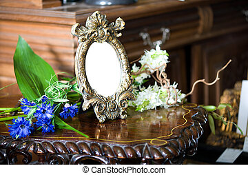 Still life with antique frame with woman's portrait and...