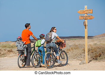 Family having a excursion on their bikes - Back view of...