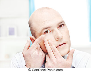 man putting contact lens in his eye