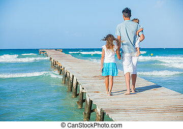 Family of three on jetty by the ocean
