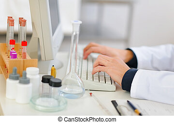 Closeup on hands of medical doctor working on computer